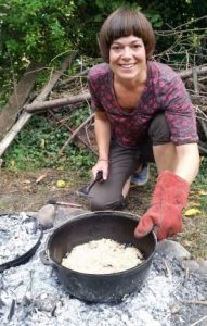 toni rogers from the team cooking apple crumble in a dutch oven on the campfire